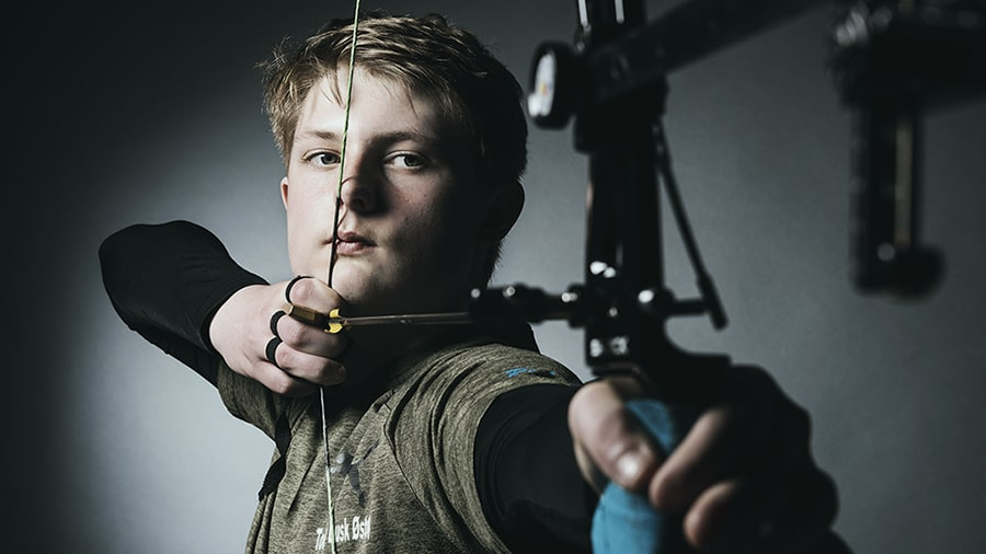 An archer holding a compound bow with it drawn.