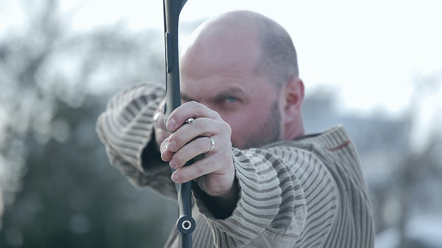 An archer holding a recurve bown dawn aiming at the viewer.