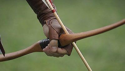 Image of a gloved hand gripping a bow and arrow.