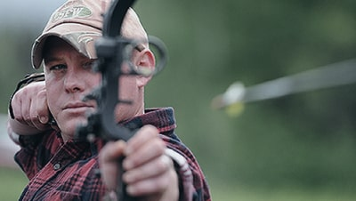 Image of a man looking down the sight of his bow just after releasing an arrow.