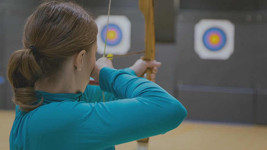 Image of a woman, bow drawn and aiming at a target.
