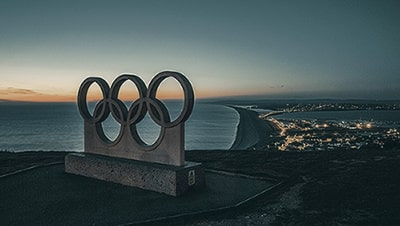 Image of a Olympics symbol statue on a cliff overlooking the ocean.