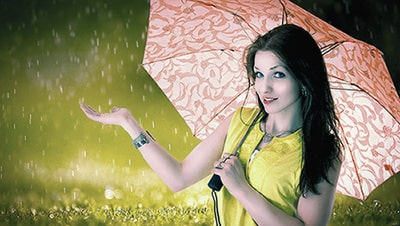 Image of a woman in a yellow jacket holding an umbrella with her hand feeling the rain.