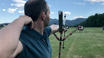 Image of a notched arrow with archery targets in the background.